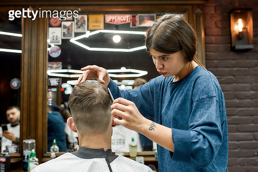Cool hairstyle. Young caucasian man getting new haircut in the modern barbershop. Professional barber girl doing haircut for her client. Beauty salon