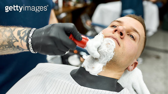 Shaving the beard. Cropped photo of a barber with tattooed arm applying shaving foam with brush on client's skin while working in the barbershop