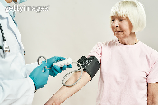 Health Checkup. Doctor in medical uniform and blue sterile gloves measuring blood pressure of senior woman, female patient