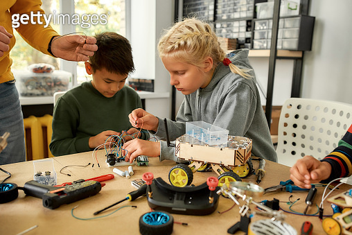 Quality and engineering. Young technicians building a robot, working with a wiring kit together with a male teacher at a stem robotics class. Inventions and creativity for kids