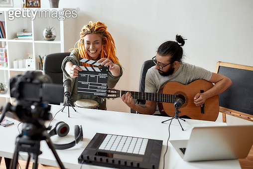Face the music. Man playing guitar and woman holding clapperboard. Couple of musicians recording video blog or vlog while making music at home