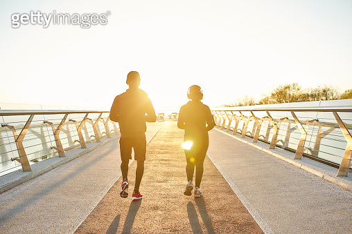 Couple running in the morning. Back view of sporty couple running together on the bridge in the early morning with warm sunlight. Full length