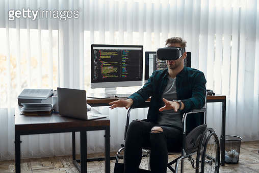 VR at work. Young male web developer in a wheelchair wearing virtual reality glasses while working at his workplace in modern office. High Tech