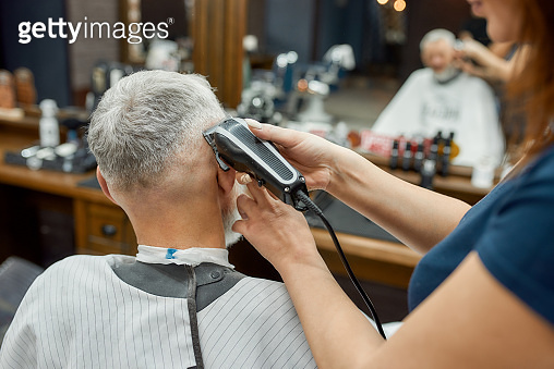 Perfect work. Barber girl using hair clipper. Making new haircut for elegant mature man sitting in armchair in the front of mirror