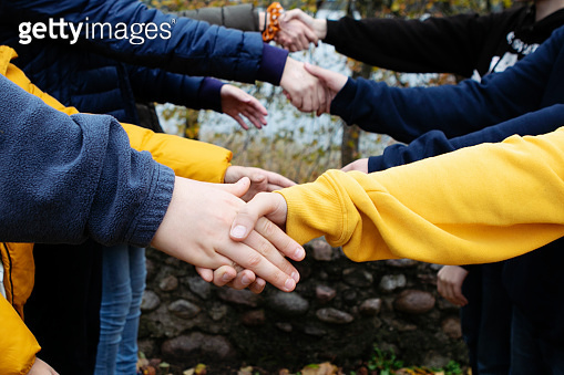 Close up of many Caucasian arms raised in the air in a row and shaking hands outdoors, friendship.