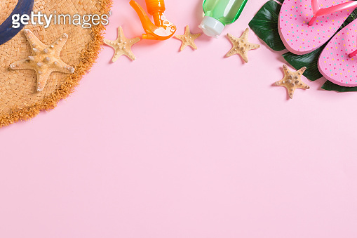 Beach accessories with straw hat, sunscreen bottle and seastar on pink background top view with copy space