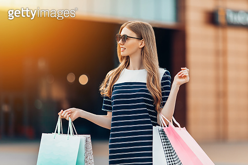 beautiful young woman with sunglasses and multicolored shopping bags is shopping on the street in front of a shopping center. Shopping, fashion