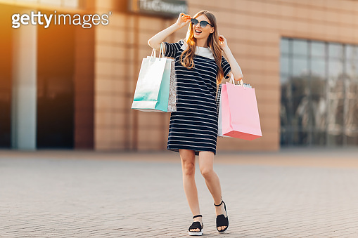 happy, beautiful young woman with sunglasses and multicolored shopping bags is shopping on the street in front of a shopping center. Shopping, fashion