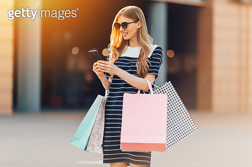attractive happy beautiful young woman wearing sunglasses, carrying shopping bags, using a smartphone and shopping in a shopping center. Shopping, fashion