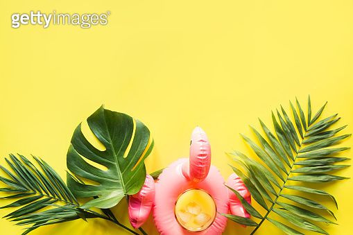 Glass of orange juice in inflatable pink flamingo on punchy pastel yellow background. Top view.