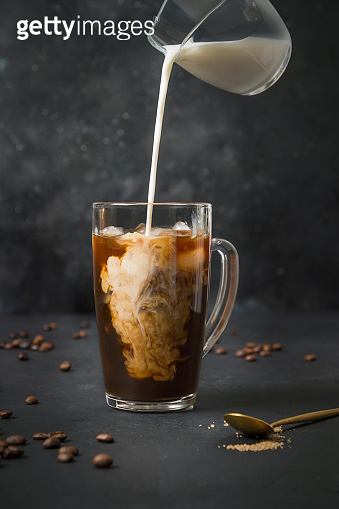 Iced latte coffee in cup glass with pouring milk on black