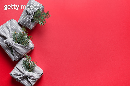 Christmas sustainable gifts wrapped in red textile on red. Xmas. Japanese Furoshiki style. View from above. Flat lay.