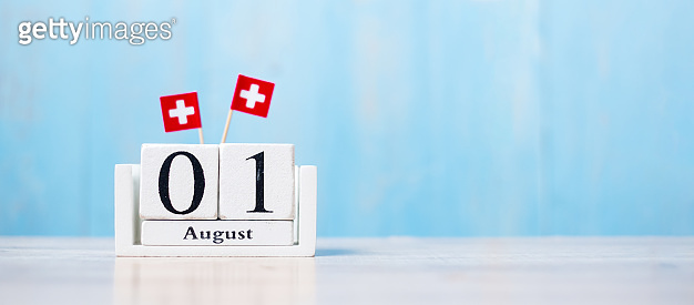 Wooden calendar of August 1st with miniature Switzerland flags. Swiss National Day and happy celebration concepts