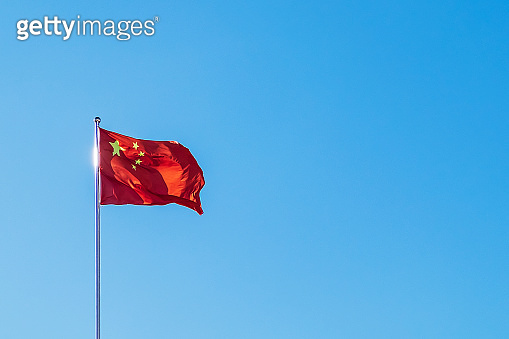 Chinese flag waving on blue sky background with copy space for text. People's republic of China national day, 1 october.