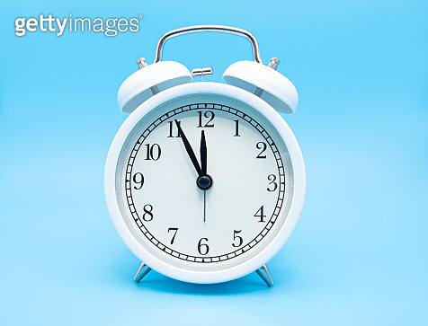 White classic alarm clock on blue background, concept picture