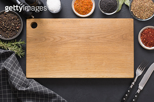 Cutting wooden board with spices and ingredients for cooking and marinade tasty dishes. Space for text. View from above.