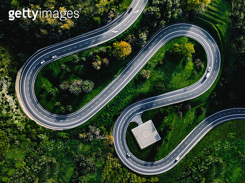 Aerial view of winding curved road with helicopter parking in Italy