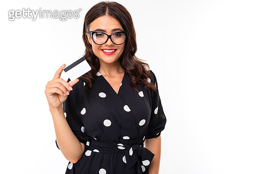 brunette in glasses holds a credit card with a mockup on a white background with copy space
