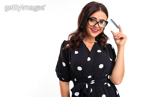 smilingbrunette in glasses holds a credit card with a mockup on a white background with copy space