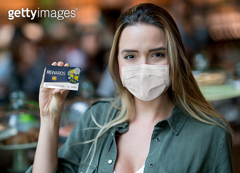 Woman at the supermarket holding a rewards card and wearing a facemask