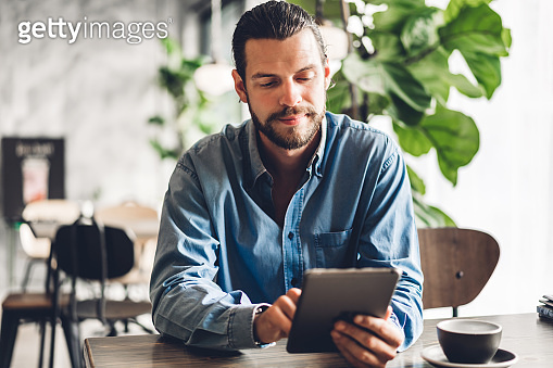 Handsome bearded hipster man relaxing using tablet computer while sitting on chair.technology and communication concept