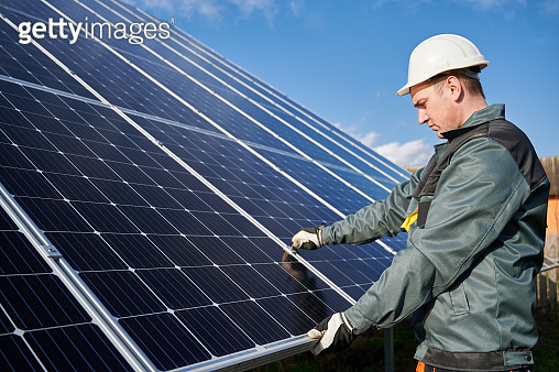 Male electrician checking photovoltaic solar panel.