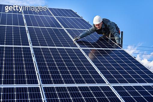 Male worker mounting solar module under beautiful sky.
