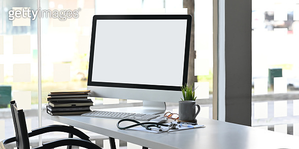 Computer monitor with white blank screen putting on doctor working desk together with stack of books, stethoscope, digital thermometer, clipboard, potted plant, glasses, mouse and keyboard