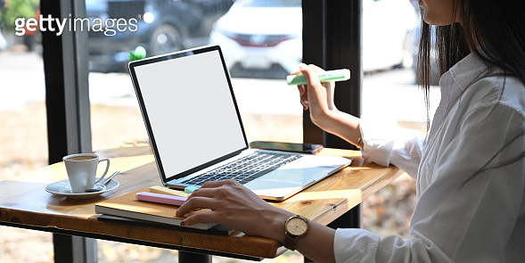 Cropped image of young secretary working with white blank screen laptop while sitting at wooden table over comfortable cafe glass wall as background. Working outside office concept.