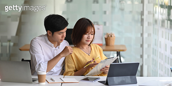 Photo of young couple working together with computer tablet and laptop, clipboard while sitting at the white working desk over modern office as background.