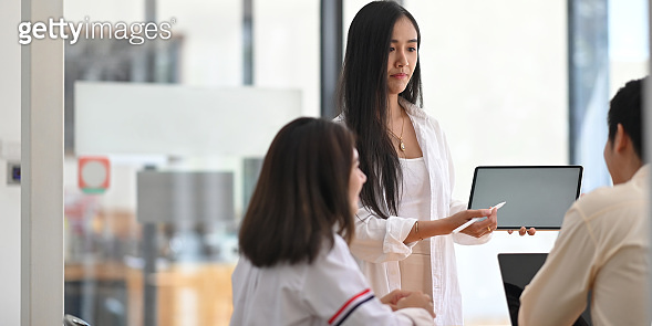 Photo of beautiful woman working as marketing standing and showing a white blank screen tablet on her hands while meeting with colleague at the modern table over orderly meeting room as background.