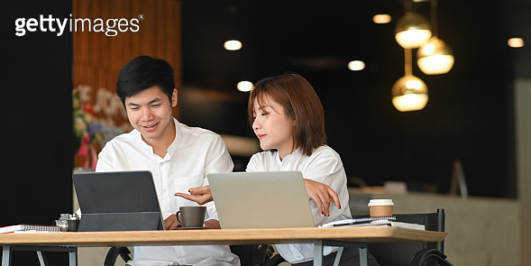 Photo of website administrator team working with computer tablet and laptop while sitting together at the modern wooden table over luxury cafe as background. Working outside the office concept.