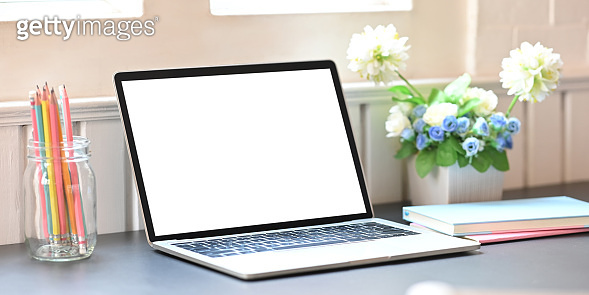 Photo of white blank screen computer laptop putting on working desk with bunch of flowers, notebook and pencil holder over comfortable living room as background. Orderly workspace concept.