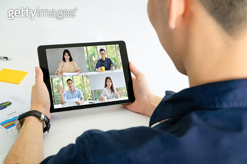 Back view of Business man using tablet for video conferencing