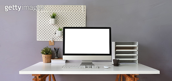 Computer monitor with white blank screen putting on white working desk and surrounded by bookshelf, wireless mouse, keyboard, coffee cup, potted plant and stack of books over room wall as background.