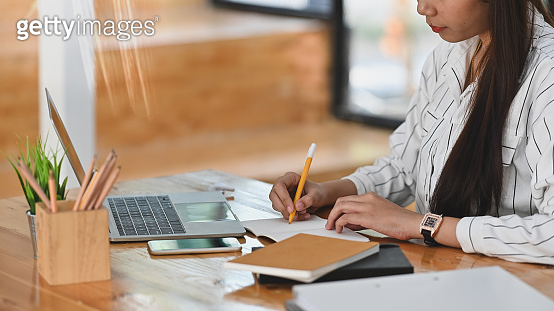 Cropped shot of young business woman while writing a report on the  wooden working desk.