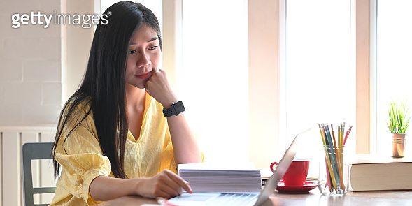 Photo of beautiful woman relaxing and using a computer laptop while sitting at the wooden working desk over comfortable living room windows as background. Student tutoring and online learning concept.