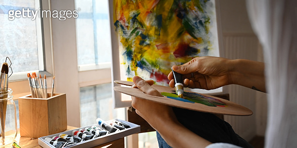 Cropped image of artist hands while holding and mixing oil color on artist palette over painting canvas and comfortable sitting room windows as background.