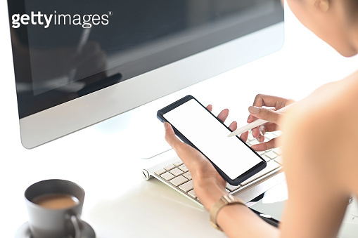 Closeup woman holding creative pen and mockup smartphone with empty screen on workspace.
