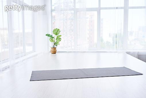 yoga room with big light window in modern flat. Yoga mat on the floor, no people