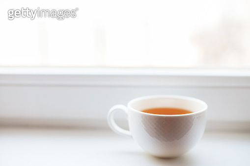 white cup with tea stands on the windowsill on the window