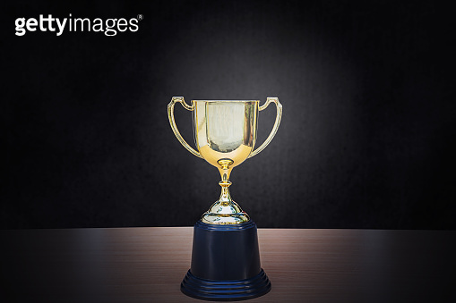 Golden trophy placed on top of old wooden table in front of dark background copy space ready for your design win concept.