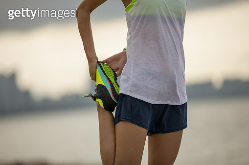 Fitness sports woman runner stretching on seaside