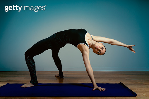 Athletic aged woman doing yoga on a blue background - the concept of a healthy lifestyle and a natural balance between the body and mental development and aging. Active old age