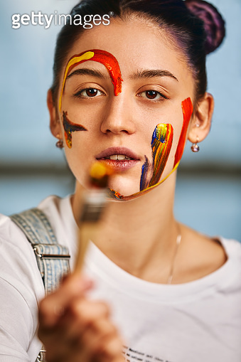 Portrait of a beautiful girl in the paint. Half-length portrait of the artist's girl with face and hands with different colors. Fashion art concept, beauty, creative people, freelance people