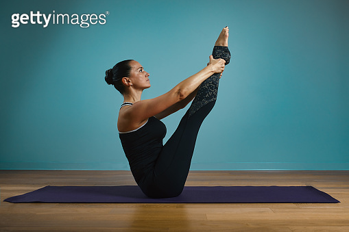 Sporty young woman doing stretching standing. Slim girl practicing yoga indoors on blue background. Calm, relax, healthy lifestyle concept