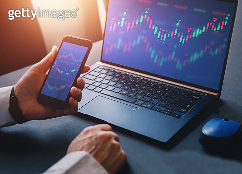 Business woman using laptop computer with financial graphs and statistics on monitor. Forex investment business.