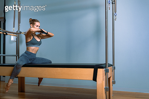 Pilates woman in reformer teaser exercise in gym indoors. Active lifestyle, body positive, beautiful color