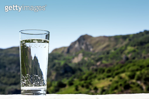 Drink glass with pouring clear water in a sunny summer day with green mountain landscape background. Healthy lifestyle, water balance control, skin care concept