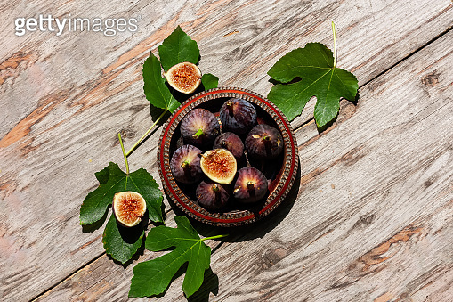 Ripe purple fig fruit with leaf in a wooden bowl on wooden background. Harvest and healthy eating concept. Selective focus. Top view.